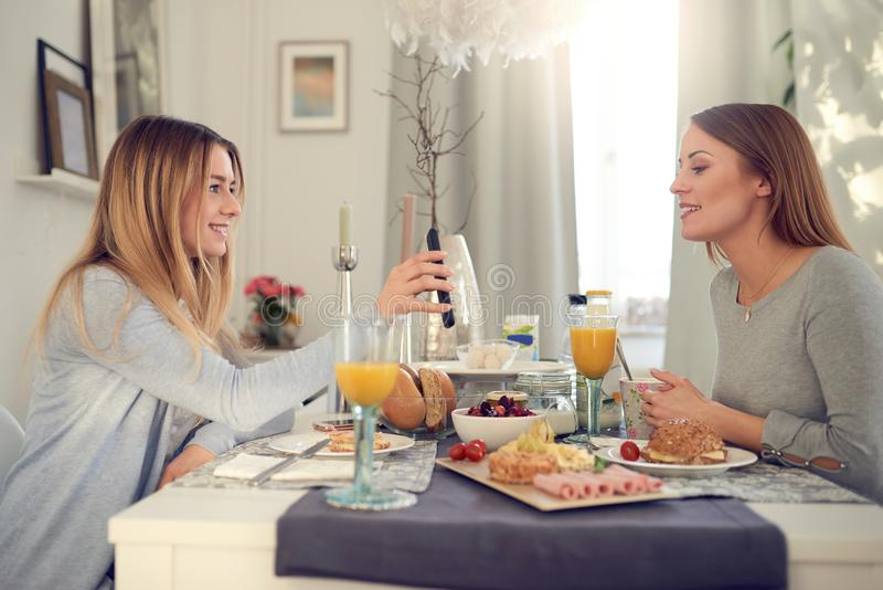 Smiling attractive young teenager showing her mother her mobile phone. As they sit enjoying a healthy breakfast together indoors at home royalty free stock photography