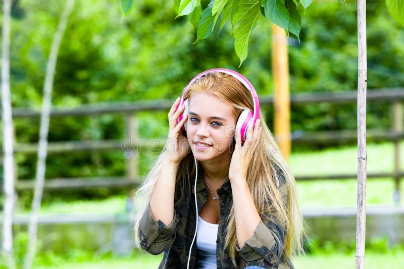 Smiling attractive young woman enjoying music. Smiling attractive young woman enjoying her music on stereo headphones, as she relaxes outdoors in a lush green royalty free stock photo