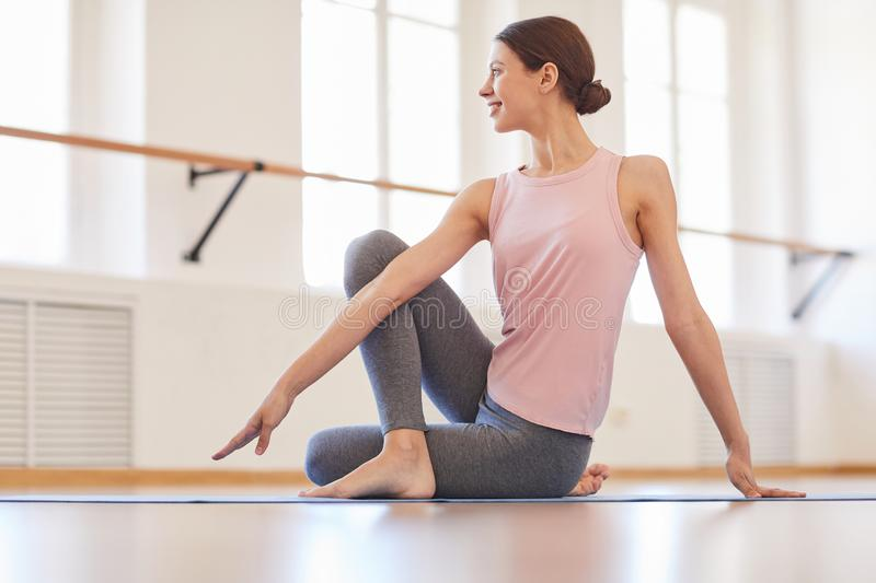 Twisting body at yoga class. Smiling attractive young woman with hair bun sitting on mat and twisting body while practicing half lord of fishes pose at yoga stock images