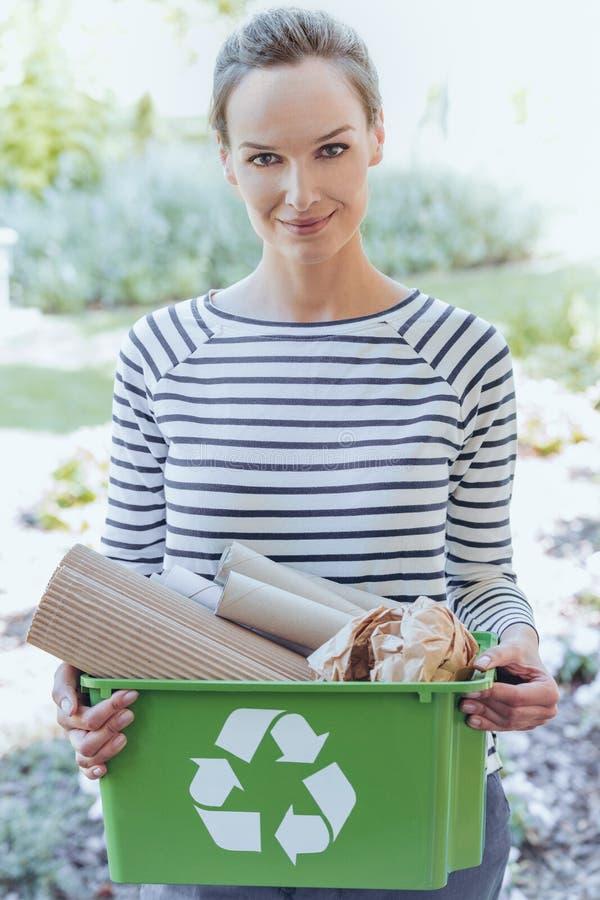 Smiling woman segregating paper junk royalty free stock photography