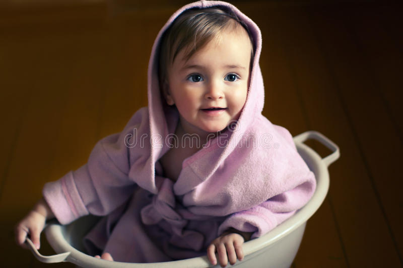 Smiling baby in a bathrobe sits in a basin. Smiling baby in pink bathrobe sits in a basin royalty free stock photo