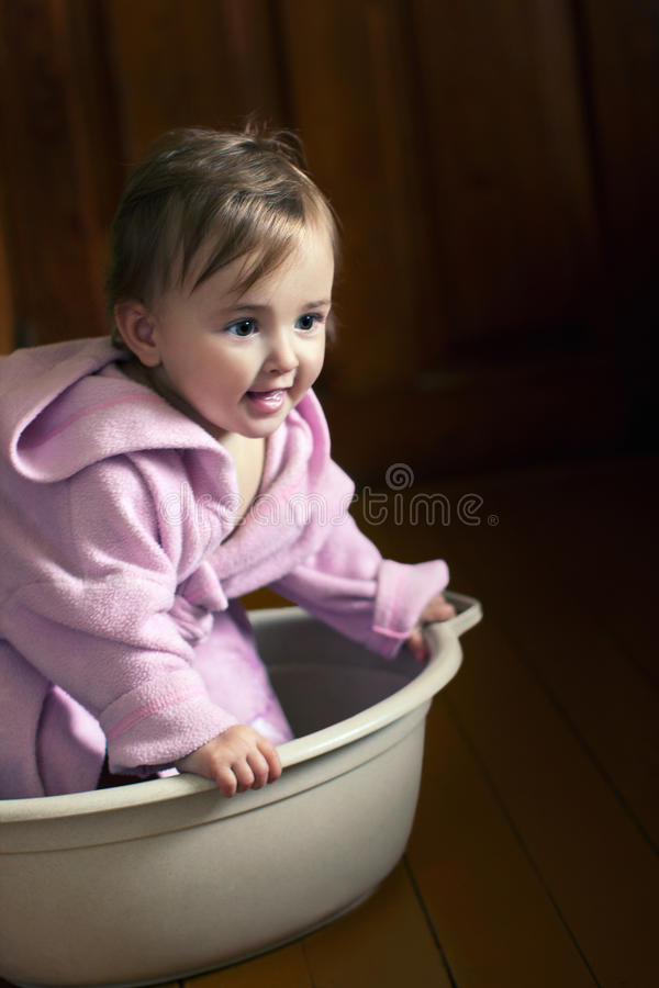 Smiling baby in a bathrobe sits in a basin. Smiling baby in pink bathrobe sits in a basin stock photo