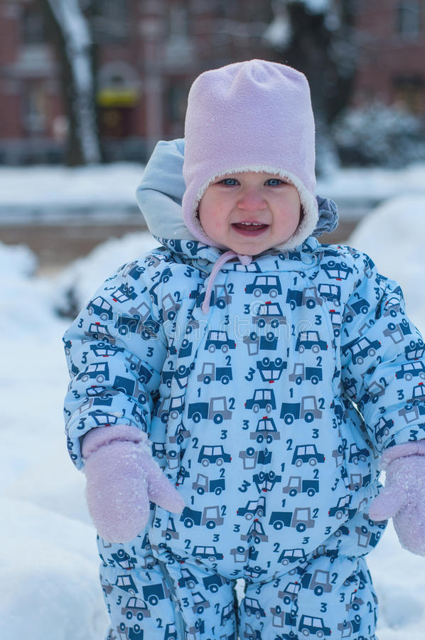 Smiling baby in blue overall, pink hat and mittens. people, children and winter concept. Portrait of a little girl in winter cloth stock photography