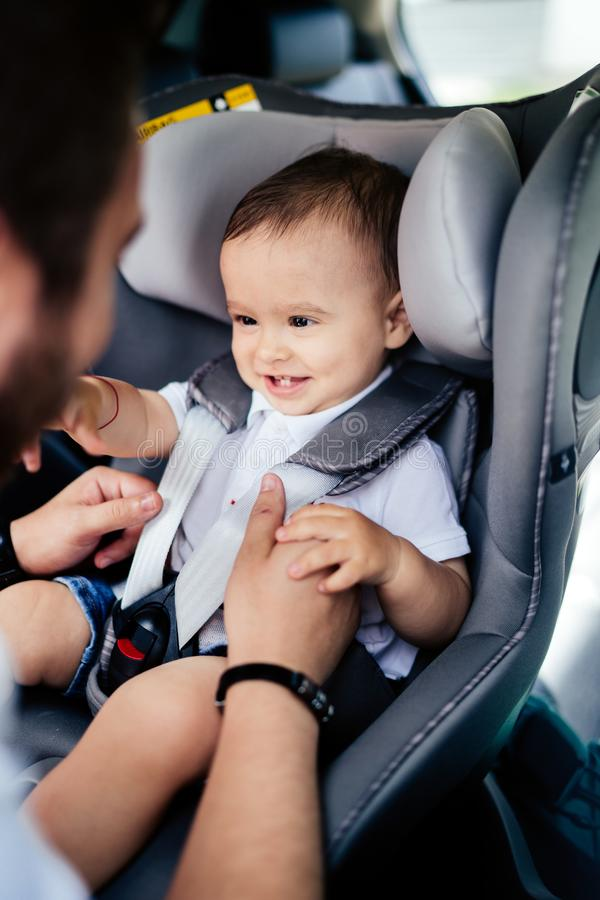 Smiling baby in child car seat going for a family roadtrip. Safety seatbelt royalty free stock photos