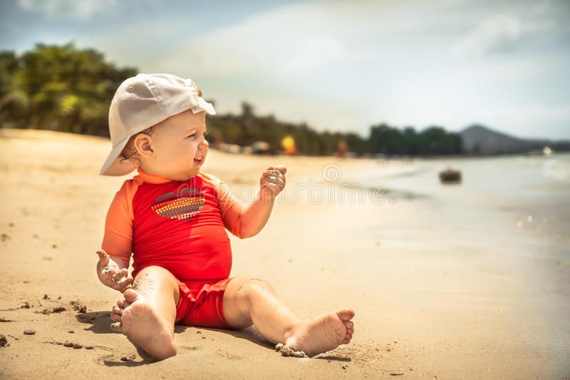 Smiling baby child kid leisure activity beach playing sand sea during hot summer holidays stock image