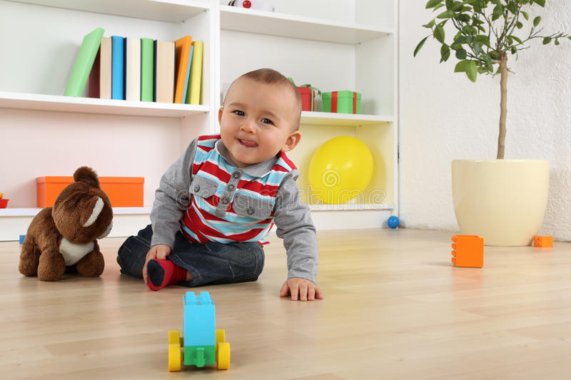 Smiling baby child playing with toys. Portrait of a smiling baby child playing with toys in children's room stock photos