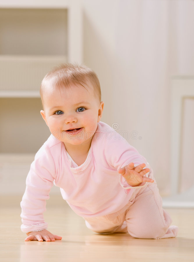 Smiling baby crawling on livingroom floor royalty free stock photos
