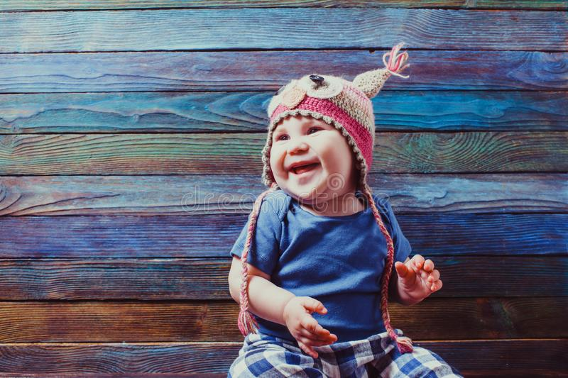 Smiling baby in cute crocheted owl hat stock images