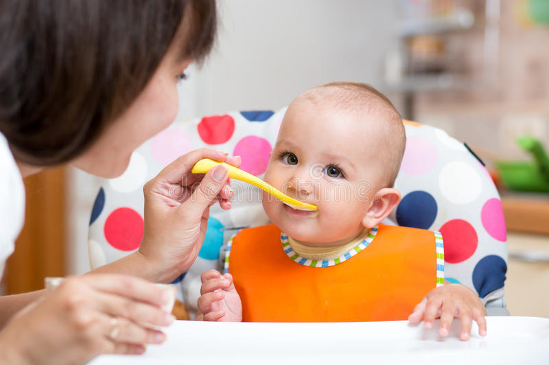 Smiling baby eating food with mom on kitchen stock images