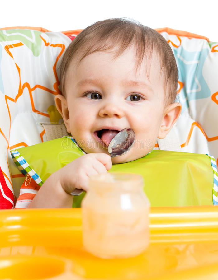 Smiling baby eating food with spoon stock images