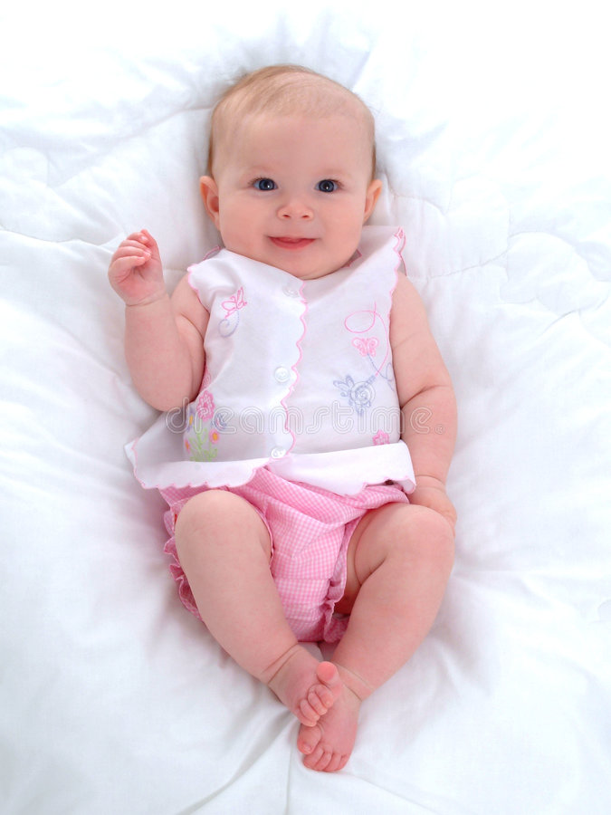 Smiling Baby Girl. Baby girl sitting in front of white background on blanket stock photos