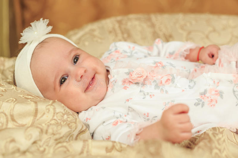 Smiling baby girl laying down stock photo
