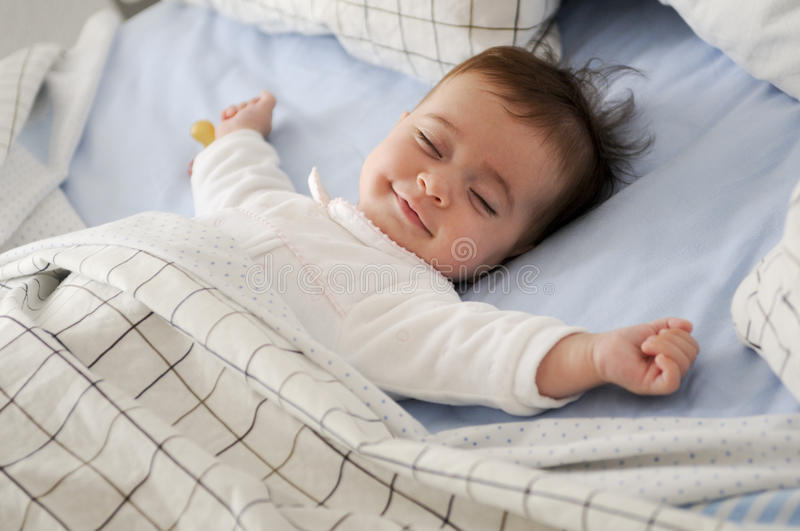 Smiling baby girl lying on a bed sleeping stock images