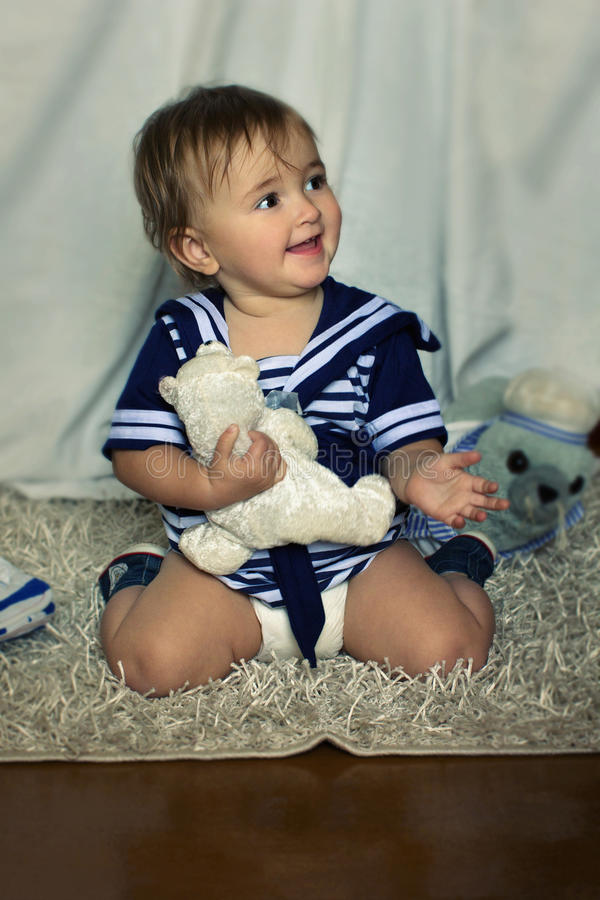 smiling baby girl in the nautical striped vest sits on the carpet stock photo