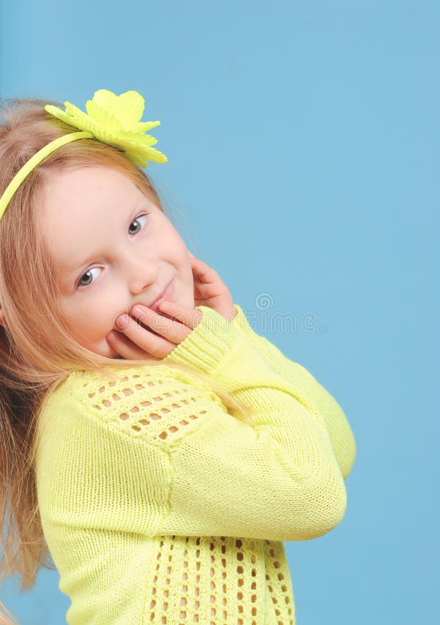 Smiling baby girl posing on blue stock photo