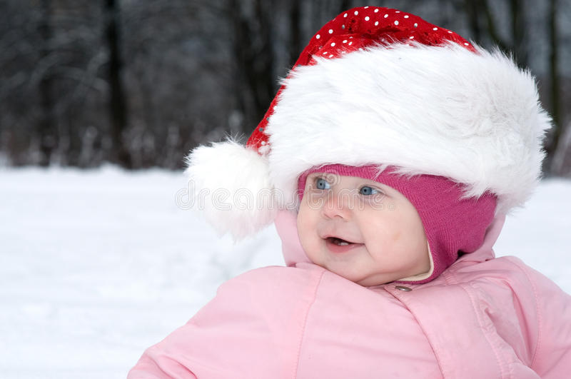 Smiling Baby Girl in red christmas hat. royalty free stock images