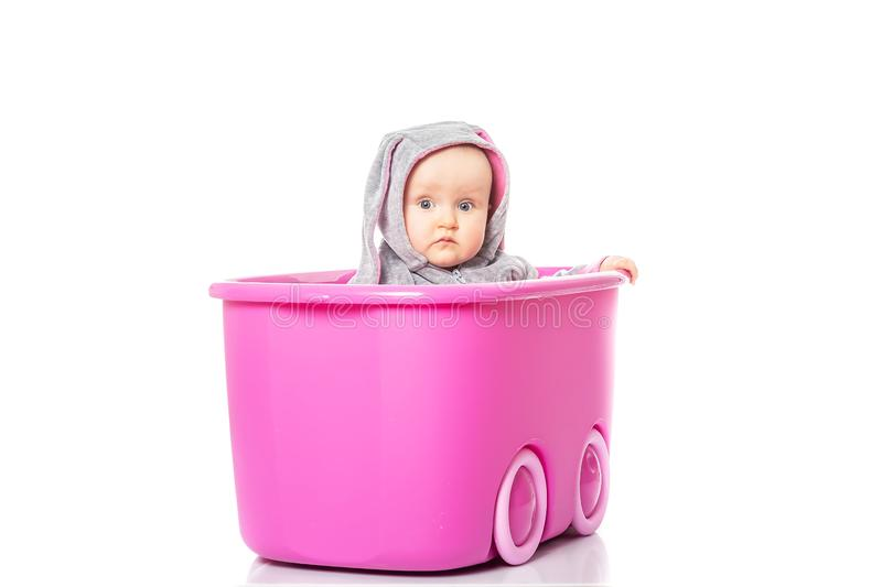 Smiling baby girl sitting inside a pink box on white background. children`s games royalty free stock image