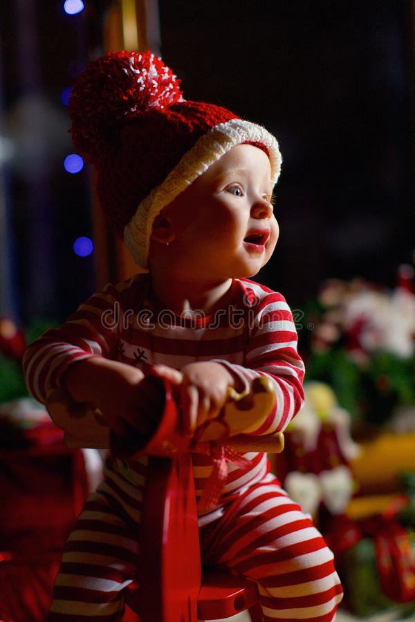 Smiling baby girl sitting on wooden hourse in a striped hat red and white color near the Christmas tree. The concept of stock images