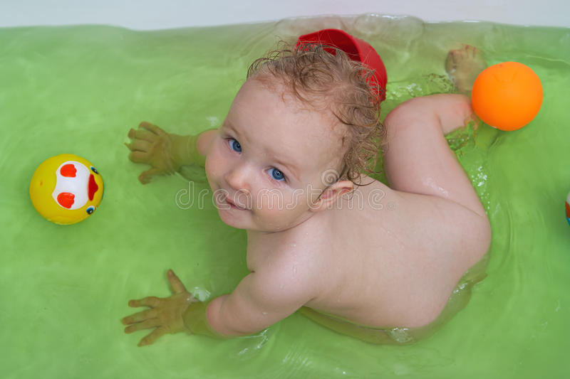 Smiling baby girl taking bath. And playing with toys royalty free stock photo