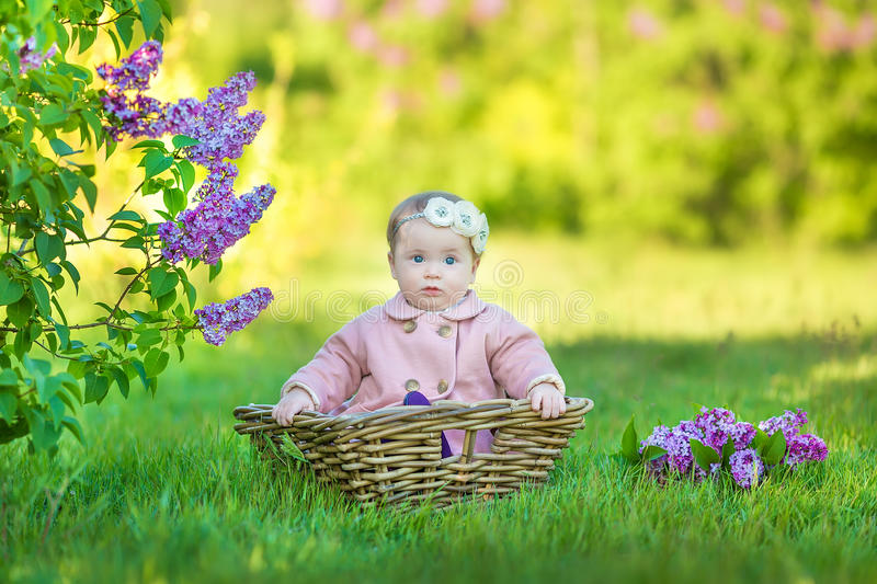 Smiling baby girl 1-2 year old wearing flower wreath, holding bouquet of lilac outdoors. Looking at camera. Summer spring time. stock image