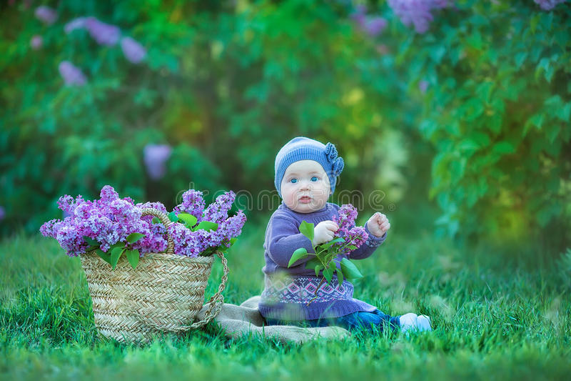 Smiling baby girl 1-2 year old wearing flower wreath, holding bouquet of lilac outdoors. Looking at camera. Summer spring time. Smiling baby girl 1-2 year old royalty free stock photography