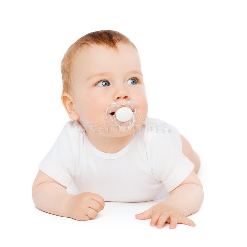 Smiling baby lying on floor with dummy in mouth royalty free stock photo