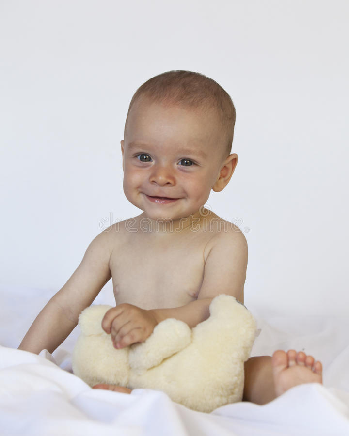 Smiling baby playing with teddy bear royalty free stock photography