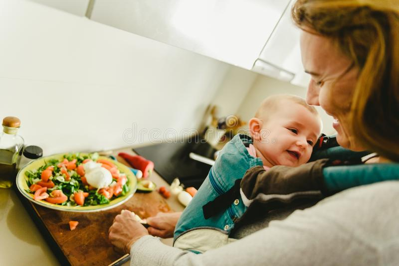 Smiling baby ported in baby carrier backpack looking at his mother while she cooks, concept of family conciliation royalty free stock photos