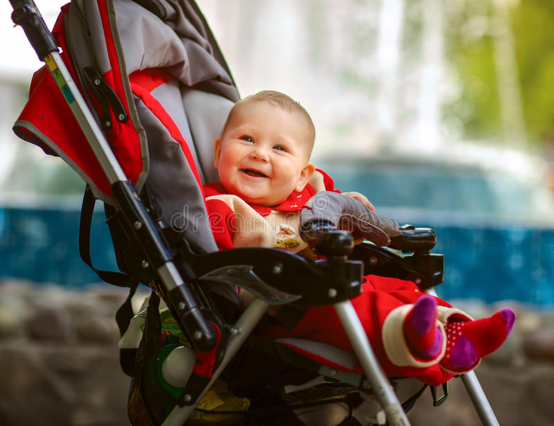 Smiling baby in sitting stroller on nature stock images