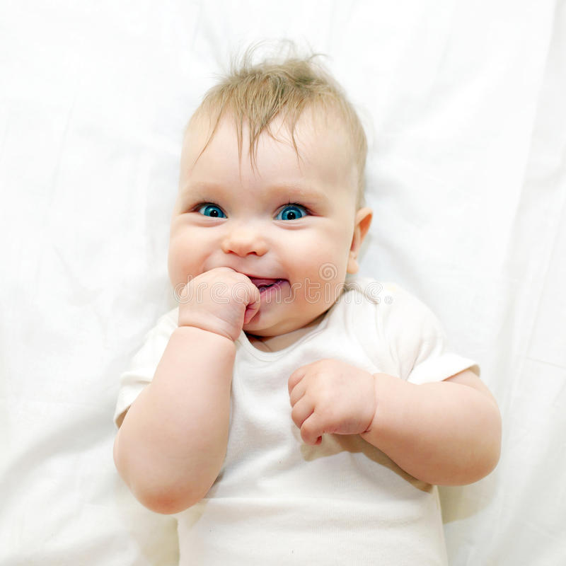 Smiling baby sucking his finger stock photos