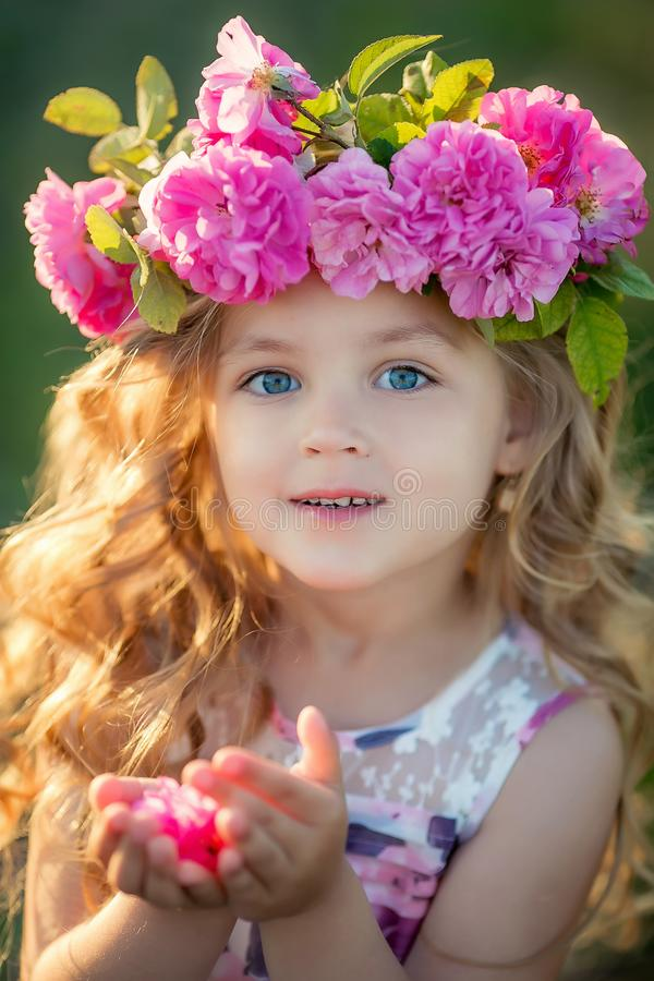 Smiling baby 3-4 year old standing with basket of flowers outdoors. Looking at camera. Summer season. stock photos