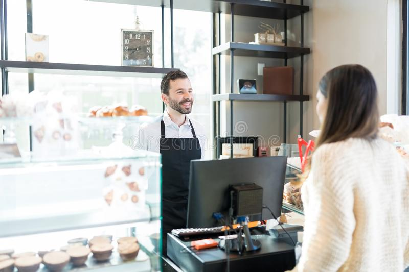 Smiling Baker With Customer In Bakery stock image