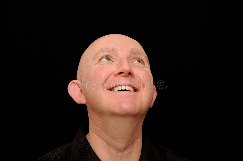 Smiling bald man looking up. A portrait of a young bald man smiling brightly as he glances upward. Black background royalty free stock photography