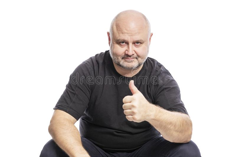 A smiling bald middle-aged man in a black T-shirt is sitting with his thumb up. Isolated over white background stock images