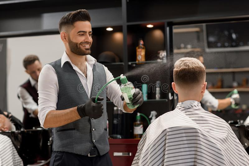 Smiling barber sprinkling water on client`s haircut using sprayer bottle. royalty free stock photo