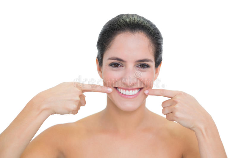 Smiling Bare Brunette Pointing At Her Mouth Stock Photo