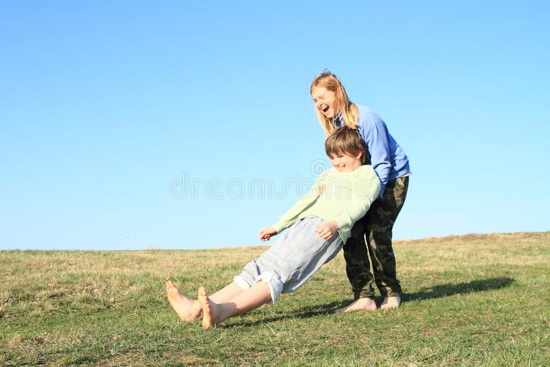Smiling kids playing trust game. Smiling barefoot kids playing trust game. Young girl with blond hair dressed in blue jacket catching to hands of young boy royalty free stock photo