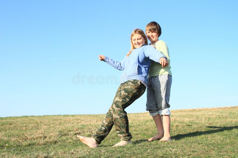 Smiling kids playing trust game. Smiling barefoot kids playing trust game. Young girl with blond hair dressed in blue jacket falling backwards to hands of young stock image