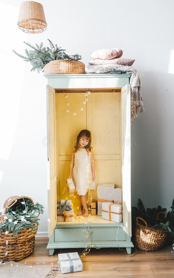 Free Smiling Barefoot Preschool Girl In White Dress Standing Inside Of Open Wardrobe Filled With Christmas Gifts Stock Photography - 193941822