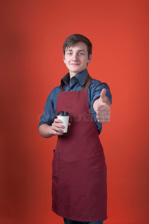 Smiling barista with dark hair in red apron holding coffee in paper cup, looking at camera and thumbing up. Handsome smiling barista with dark hair in red apron stock images