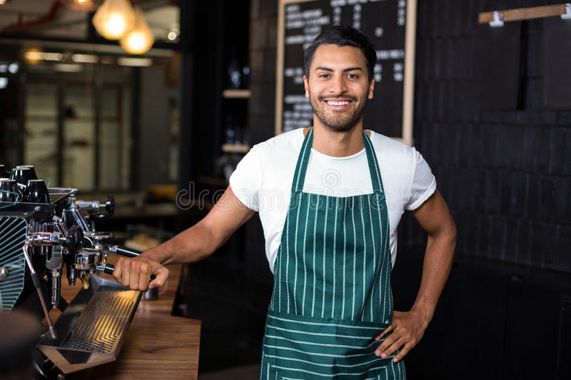 Smiling barista standing next coffee machine royalty free stock photography