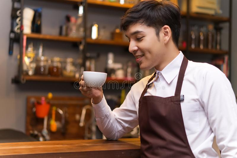 Smiling barista wearing an apron trying espresso in coffee shop. stock image
