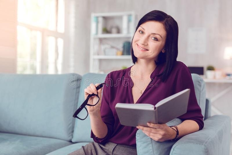 Smiling beaming charming mid-aged female holding an open book. royalty free stock photo