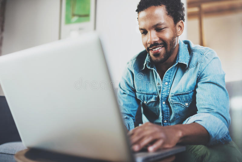 Smiling bearded African man spending free time in sofa and using laptop at modern home.Concept of young people enjoying stock images