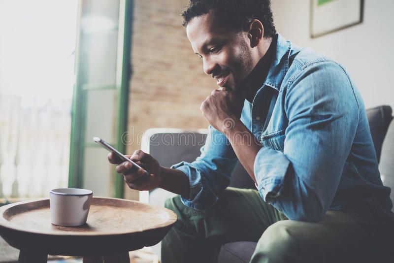 Smiling bearded African man using smartphone while sitting on sofa at home.Concept people working with mobile gadget. Blurred background royalty free stock images