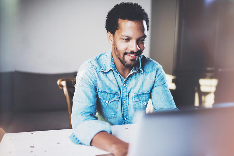Smiling bearded African man working on laptop while spending time at coworking office.Concept of young business people stock photography