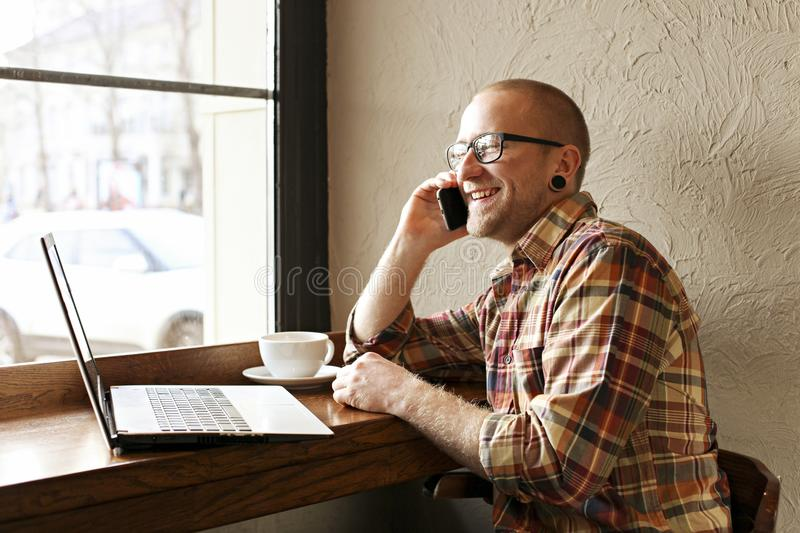 Smiling bearded businessman wearing casual hipster clothing using laptop and cell smartphone in coffe house. stock photo