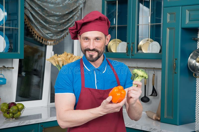 Smiling bearded chef holds paprika and cabbage. handsome guy prepared fresh paprika for lunch royalty free stock photo
