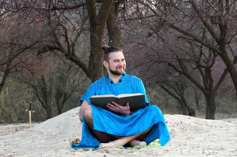 Smiling bearded man in blue kimono sitting with large book royalty free stock photography