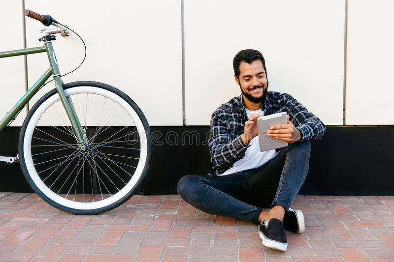 Smiling bearded man browsing websites while using his tablet, outdoors royalty free stock images